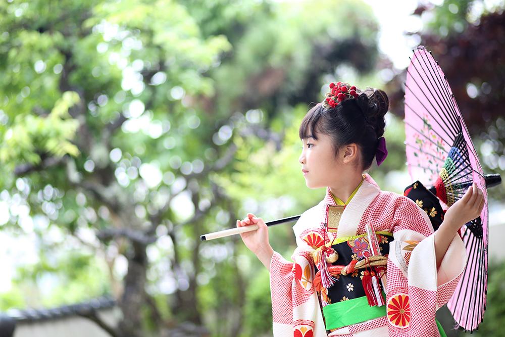 和傘を肩にかけた赤い着物の女の子