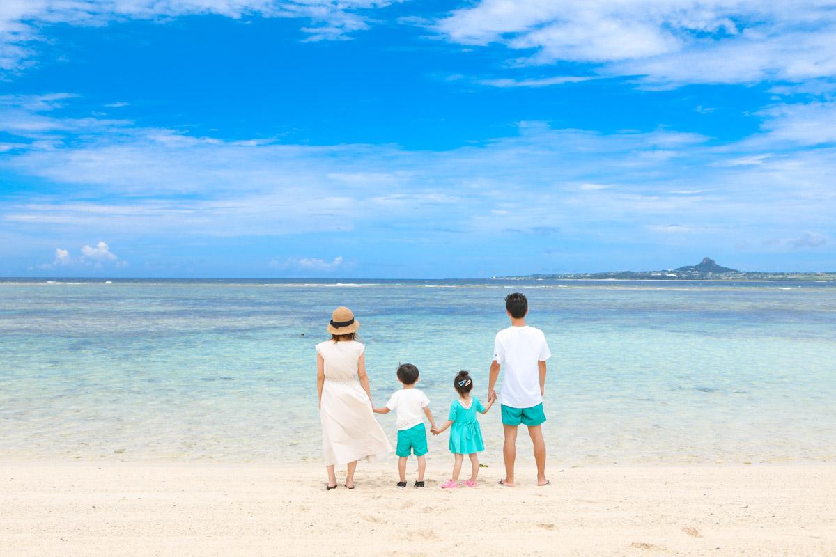 エメラルド色の美しいビーチで家族写真撮影