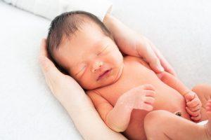 パパとママの手を入れた新生児の写真